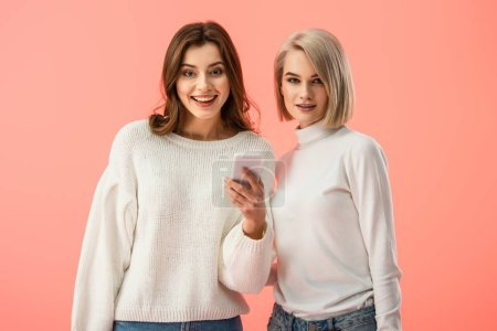 Photo for Cheerful brunette girl holding smartphone and standing near blonde friend isolated on pink - Royalty Free Image