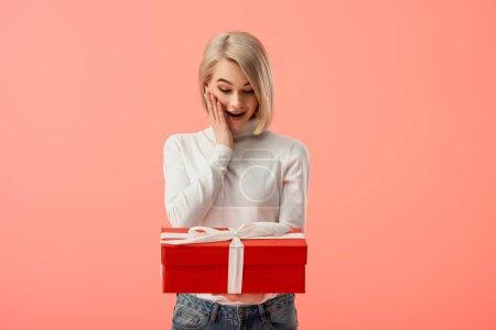 Photo pour Choqué blonde jeune femme regardant coffret rouge isolé sur Rose - image libre de droit