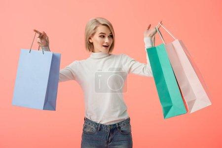 Photo pour Surpris blonde jeune femme tenant des sacs isolés sur Rose - image libre de droit