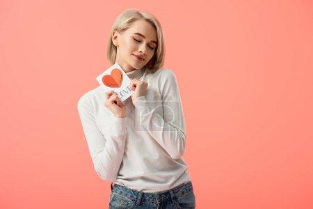 Photo pour Joyeuse blonde jeune femme tenant carte de voeux en se tenant debout avec les yeux fermés isolés sur Rose - image libre de droit