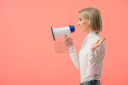 Photo pour Femme blonde gaie parlant en mégaphone isolé sur rose - image libre de droit