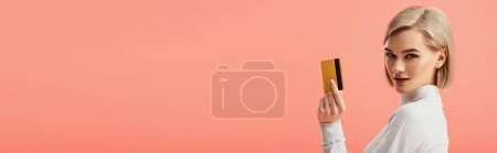 Photo for Panoramic shot of attractive blonde woman holding credit card isolated on pink - Royalty Free Image