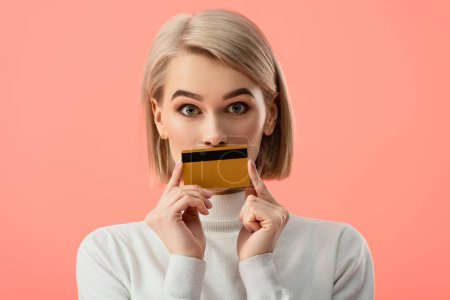 Photo for Surprised blonde woman covering mouth with credit card isolated on pink - Royalty Free Image