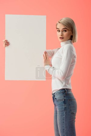 Photo for Surprised blonde woman holding blank placard isolated on pink - Royalty Free Image