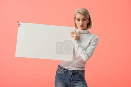 Photo for Surprised blonde girl holding blank placard isolated on pink - Royalty Free Image