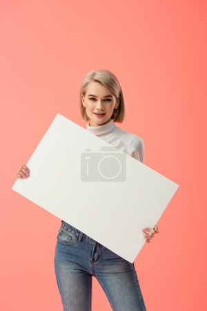 Photo for Happy blonde girl holding blank placard isolated on pink - Royalty Free Image