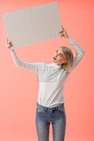 Photo pour Surpris jeune femme blonde tenant une pancarte vierge isolé sur rose - image libre de droit
