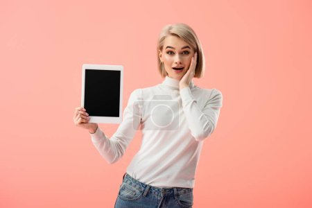 surprised blonde woman holding digital tablet with blank screen isolated on pink