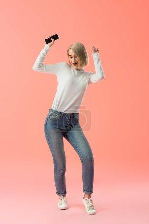 Photo pour Joyeuse fille blonde tenant smartphone et célébrant triomphe sur fond rose - image libre de droit