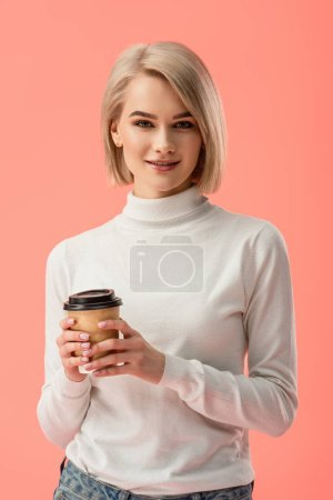 Photo for Attractive blonde girl holding paper cup with drink isolated on pink - Royalty Free Image