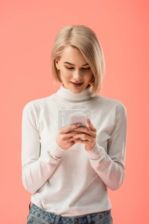 Photo for Attractive blonde woman using smartphone isolated on pink - Royalty Free Image