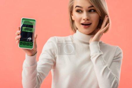Photo pour Foyer sélectif de femme blonde surprise tenant smartphone avec application de réservation à l'écran isolé sur rose - image libre de droit