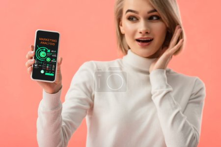 Photo for Selective focus of surprised blonde woman holding smartphone with marketing analysis on screen isolated on pink - Royalty Free Image