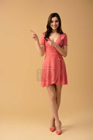 Photo pour Gai brunette femme pointant avec les doigts tout en se tenant sur fond brun - image libre de droit
