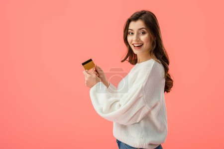 Photo for Happy brunette girl holding credit card isolated on pink - Royalty Free Image