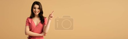 Photo for Panoramic shot of cheerful brunette woman pointing with finger while standing isolated on brown - Royalty Free Image