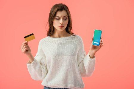 Photo pour Attrayant brunette fille tenant carte de crédit tout en regardant smartphone avec twitter app à l'écran isolé sur rose - image libre de droit