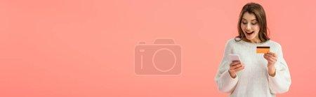 Foto de Toma panorámica de sorpresa chica morena con tarjeta de crédito y teléfono inteligente aislado en rosa - Imagen libre de derechos