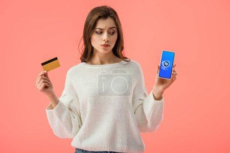 Photo pour Attrayant brunette fille tenant carte de crédit tout en regardant smartphone avec application shazam à l'écran isolé sur rose - image libre de droit
