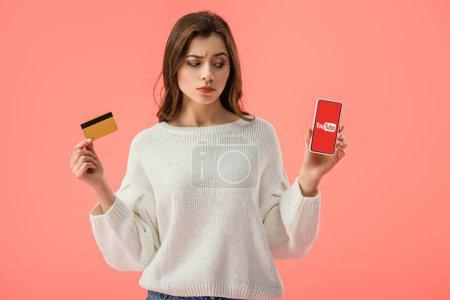 Photo pour Jolie fille brune détenant la carte de crédit tout en regardant les smartphone avec l'application youtube sur écran isolé sur Rose - image libre de droit