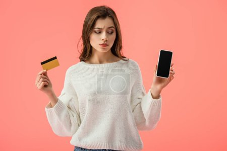 Photo for Attractive brunette girl holding credit card while looking at smartphone with blank screen isolated on pink - Royalty Free Image