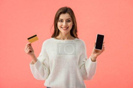Photo pour Heureuse fille brune tenant carte de crédit tout en regardant smartphone avec écran vide isolé sur rose - image libre de droit
