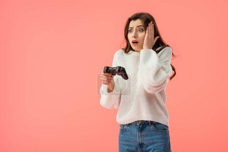 shocked girl holding joystick while standing isolated on pink