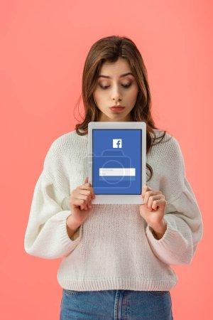 Photo pour Belle jeune femme tenant une tablette numérique avec facebook app sur écran isolé sur Rose - image libre de droit