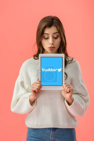 überraschte junge Frau hält digitales Tablet mit Twitter-App auf dem Bildschirm isoliert auf rosa