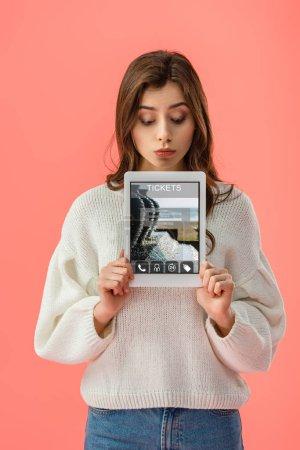 Photo pour Surprise jeune femme tenant tablette numérique avec l'application billets à l'écran isolé sur rose - image libre de droit