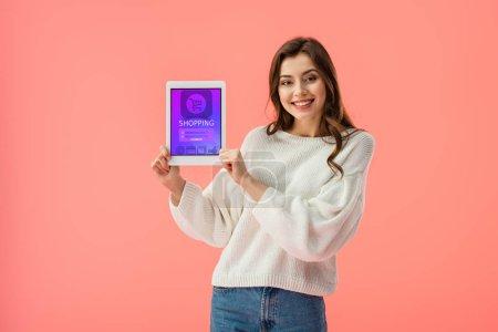 Photo pour Joyeuse jeune femme tenant tablette numérique avec app shopping à l'écran isolé sur rose - image libre de droit