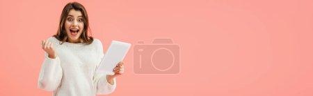Foto de Toma panorámica de sorprendido y hermosa mujer joven con tableta digital aislada en rosa - Imagen libre de derechos