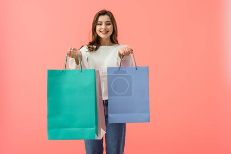 Photo for Smiling woman in white sweater and jeans holding shopping bags isolated on pink - Royalty Free Image