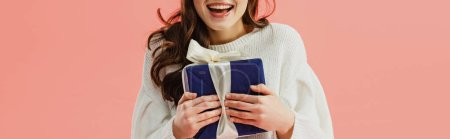 cropped view of woman in white sweater holding gift box isolated on pink