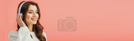 Photo pour Plan panoramique de femme souriante et séduisante en pull blanc écoutant de la musique avec écouteurs isolés sur rose - image libre de droit
