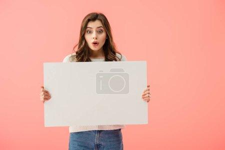 Photo pour Surpris et belle femme tenant le conseil vide avec l'espace de copie isolé sur rose - image libre de droit