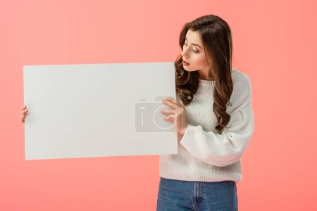 brunette and beautiful woman holding empty board with copy space isolated on pink