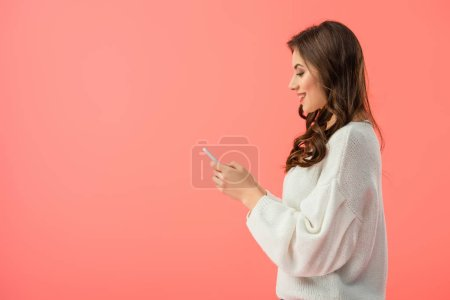 Photo for Smiling and attractive woman in white sweater holding smartphone isolated on pink - Royalty Free Image