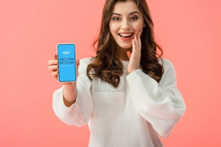 Photo for Selective focus of woman in white sweater holding smartphone with skype app on screen isolated on pink - Royalty Free Image