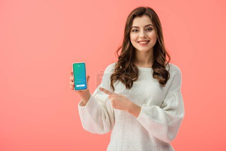 Photo for Woman in white sweater pointing with finger at smartphone with twitter app on screen isolated on pink - Royalty Free Image