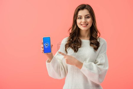 Photo for Woman in white sweater pointing with finger at smartphone with shazam app on screen isolated on pink - Royalty Free Image