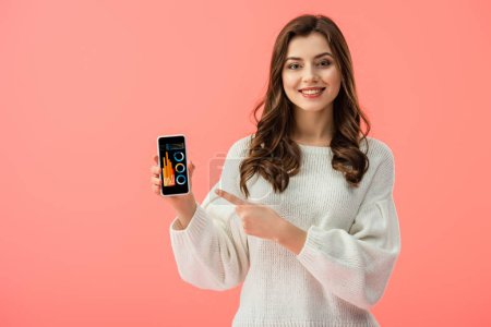 Photo for Woman in white sweater pointing with finger at smartphone with charts and graphs on screen isolated on pink - Royalty Free Image