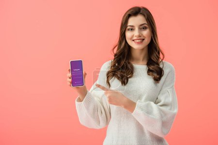 Photo for Woman in white sweater pointing with finger at smartphone with instagram app on screen isolated on pink - Royalty Free Image