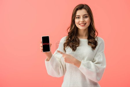 Photo for Woman in white sweater pointing with finger at smartphone with netflix app on screen isolated on pink - Royalty Free Image