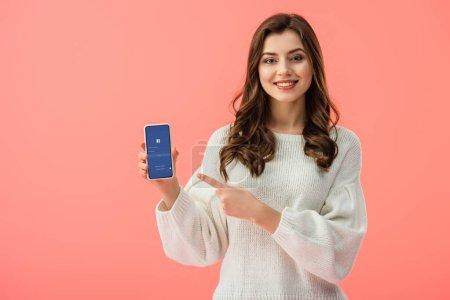 Photo pour Femme en chandail blanc pointant avec le doigt au smartphone avec l'application facebook sur écran isolé sur Rose - image libre de droit