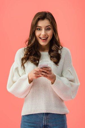 Photo pour Jeune femme souriante en pull blanc tenant smartphone isolé sur rose - image libre de droit