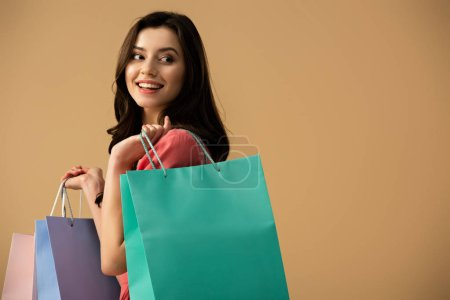 Photo for Smiling and beautiful woman holding shopping bags isolated on beige - Royalty Free Image