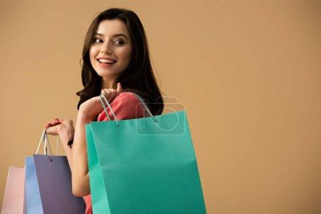 Photo pour Souriante et belle femme tenant des sacs isolés sur beige - image libre de droit