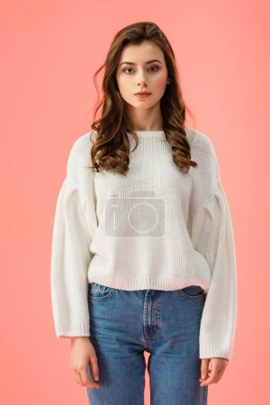brunette and attractive woman in white sweater looking at camera isolated on pink