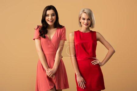 Photo pour Femmes belles et souriantes en robes rouges, regardant la caméra isolée sur beige - image libre de droit